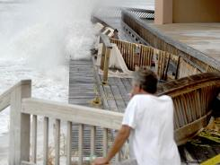 A resident of Jetty East Condominiums in Destin, Fla., watches as a wave hits the parking garage of the condominium on Wednesday.