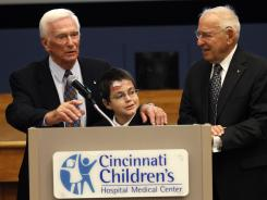 Astronauts Gene Cernan, left, and Jim Lovell, right, joined Shane DiGiovanna, 14, of Montgomery, Ohio, who has been treated for a fragile skin condition called epidermolysis bullosa, for the launch of the Neil Armstrong New Frontiers Initiative at Cincinnati Children's Hospital and Medical Center.