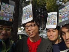 Apple fans wait in line in front of a Softbank Mobile shop in Tokyo to buy the iPhone 4S on its launch day in Japan in October 2011.