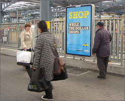 People cross in front of an advertisement promoting New York City tourism at a rail station in Dublin. The advertisement is part of an ambitious campaign to promote the Big Apple around the globe.