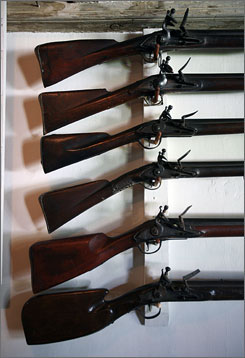 A collection of muskets from various periods is displayed on the wall in the taproom at the Buckman Tavern.