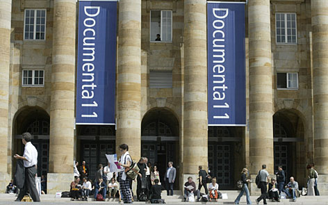 People stand and walk in front of the municipal hall of Kassel, Germany, in June 2002. Dokumenta, a major contemporary art event held every five years, runs June 16-Sept. 23.