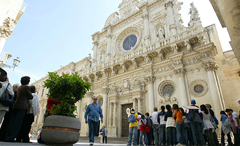 Tourists visit the Santa Croce Basilica in Lecce, in southern Italy's Puglia region.