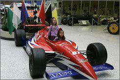 Start your engines: Twins Audrey, front and Adalyn, 5, of Fishers, Ind., have their photo taken in an Indy 500 car on display at the Indianapolis Motor Speedway Museum.