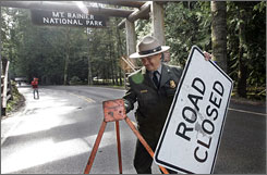 "Grand reopening: Chief ranger Chuck Young removes the ""road closed"" sign at the Nisqually entrance to Mount Rainier National Park"
