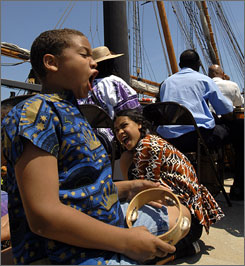 "Amistad Cinque Meeks of Manhattan, foreground, yells out the word ""freedom"" during during a farewell celebration for the Amistad in New Haven, Conn. Meeks, who was named after the Amistad, travelled with his family from New York to watch it depart."