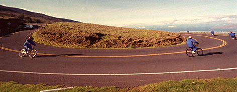 A bicycle tour group negotiates a switchback on the winding road descending from Maui's Haleakala volcano. Recent cycling deaths have led to a suspension of the popular tours.