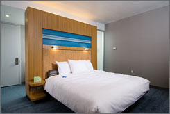 Sleek and boutique: Platform beds at Aloft hotels will have headboards made from cork. Old-fashioned bedside alarm clocks add a fun and kitschy touch.