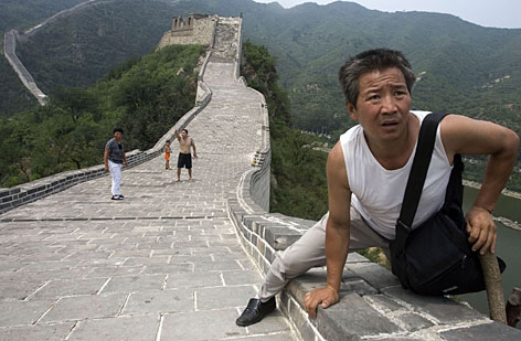 A Chinese visitor navigates a section of the Great Wall; climbing, graffiti and overdevelopment are threatening the ancient landmark.
