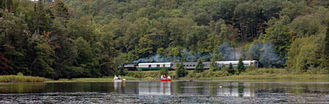 Canoeists watch the Adirondack Scenic Railroad train as they paddle on Moose River outside Old Forge, N.Y.