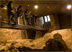 Visitors look at the remains one of the early Christian burial chambers from the 4th century.