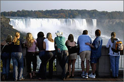 Down a cliff: Tourists view Niagara Falls from the Canadian side of the border.