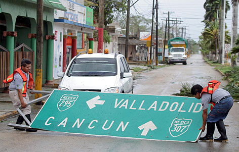 Municipal workers pick up a road sign in the Mexican town of Felipe Carrillo Puerto after Hurricane Dean made landfall on the southern Yucatan peninsula.