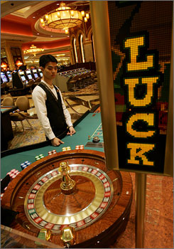 An employee stands next to the gambling table inside the casino during the opening ceremony of the Venetian Macao Resort Hotel in Macau.