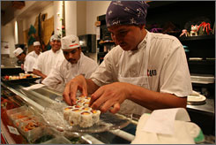 Santos Villanueva, right, plates sushi with Henry Soto, left, at Tako Grill in Bethesda, MD., where six out of seven chefs are from Central America.