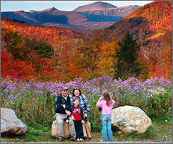 Wildflowers, fall foliage and 6,288-foot Mt. Washington serve as a backdrop for Jim and Kathleen Gannon and their son James as their daughter Katarina snaps a picture at Crawford Notch State Park in New Hampshire.