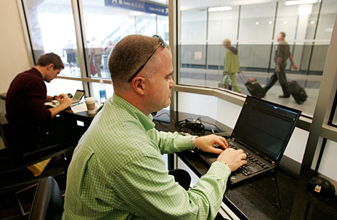 Business traveler Tim Severns, of Las Cruces, N.M., keeps up with his workload during a layover at Dallas-Fort Worth International Airport in Grapevine, Texas.