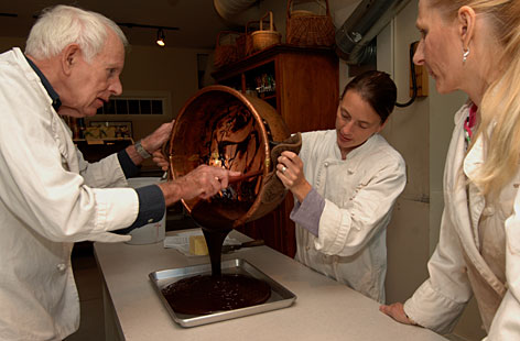 Shall I pour? Fritz and Cindy Churm mix a batch of chocolate at Laughing Moon Chocolates with owner Leigh Williams, center, in Stowe, Vt.
