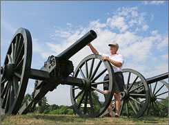 Thomas G. Clemens, a private guide for hire at Antietam National Battlefield in Sharpsburg, Md., stands along a row of artillery cannons.