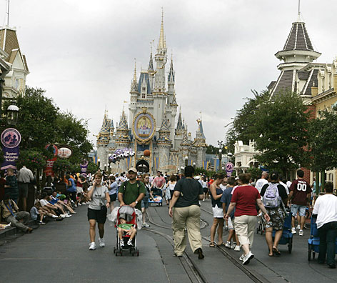 Down on Main Street: Visitors to Walt Disney World's Magic Kingdom gather for the popular afternoon parade. The whole Disney phenom started 36 years ago with one theme park and two hotels.
