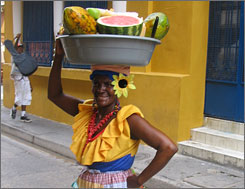 Fresh fruit: A palenquera, one of the city's iconic street vendors, pauses outside a Colonial home as she makes her morning rounds.