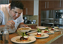 "Marcel Martinez, a personal chef who works for Exclusive Resorts, prepares lunch at an Exclusive Resorts residence inside the ""Bath Club"" in Miami, Fla."