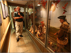 Museum curator Jerry Raisor leads a group past a diorama of Daniel Boone with native Americans during a tour of the new Fort Boonesborough State Park museum in Boonesborough, Ky.