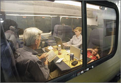 Summer travelers use laptop computers and read books while the Amtrak Acela Express, en route to Boston, makes a stop in New York's Penn Station.