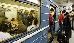 Passengers get off a train of the Russian capital's subway, which stands under large photos of, from left, heavy industries commissar Sergo Ordzhonikidze, Josef Stalin and Lazar Kaganovich, who supervised construction of the early lines.