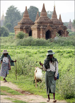 Locals walk past temples in Bagan, Myanmar. Life has almost return to normal in Mynamar after authorities violently put down pro-democracy protests, led by Buddhist monks, in late September.