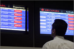 An airline passenger watches for flight delays on monitors at LaGuardia Airport in New York.