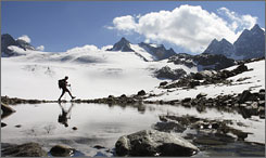 A hiker walks near the Silvretta glacier in the Swiss Alps near the town of Klosters, Switzerland.
