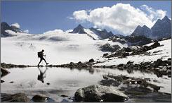 A hiker walks near the Silvretta glacier in the Swiss Alps near the town of Klosters, Switzerland.