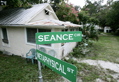 Decorative street signs stand outside the house owned by Victor Vogenitz in Cassadaga, Fla.   Vogenitz  is a self-proclaimed physical phenomenon medium and healer and his home is on a 57-acre camp established 113 years ago that is filled with people who claim they talk to the dead.