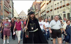 Tour guide Hans-Georg Baumgartner, center, stars in his role as the Night Watchman of Rothenburg, Germany.