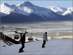 Snowboarders ski down the slope at the Alyeska Resort in Girdwood, Alaska. The Turnagain Arm, and Kenai Mountains are seen in the background.