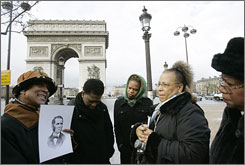 Tour guide Ricki Stevenson, left, an Oklahoma native, holds a portrait of William Wells Brown, a 19th-century former slave turned abolitionist, while speaking to visitors near the Arc de Triomphe in Paris.
