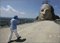 Ace Crawford walks along the arm section of sculptor Korczak Ziolkowski's carving of Sioux warrior Crazy Horse in a granite mountain at Crazy Horse Memorial in the Black Hills of South Dakota.