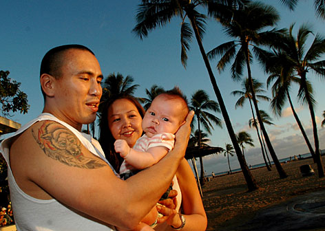 Alaskans Jeremy Esmailka and his wife Deanza Hjalseth stand with their baby Sienna, on Waikiki beach in Honolulu, Hawaii.