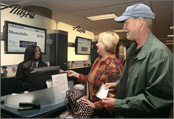 Andrea McWashington checks in Bob Frith and his wife Linda for their flight to Hawaii. The Friths, like many Alaskans leave the cold behind and travel to sunny Hawaii for vacation.