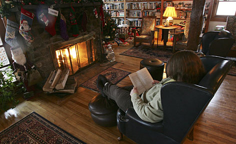 "Innkeeper Grace Newman reads a book in front of the fireplace at the Highlands Inn in Bethlehem, N.H., which she calls a ""lesbian paradise.""   Just after the stroke of midnight on the first of January, civil union ceremonies occurred across the state, including two at the Inn, in front of the fireplace."