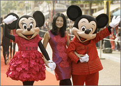 Mickey Mouse and Minnie Mouse hold hands with Hong Kong fashion designer Vivienne Tam as they display their Chinese New Year costumes designed by Tam.
