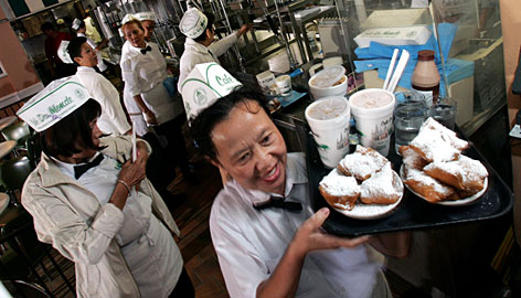 Hoisting the beignets: Dung Hguyen delivers the doughy, sugary treats at Caf Du Monde in New Orleans.