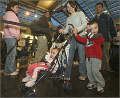 A new book by a traveling mom offers tips for traveling with young children. Pictured here, the Cornell family of Dighton, Mass., make their way through an airport security line.