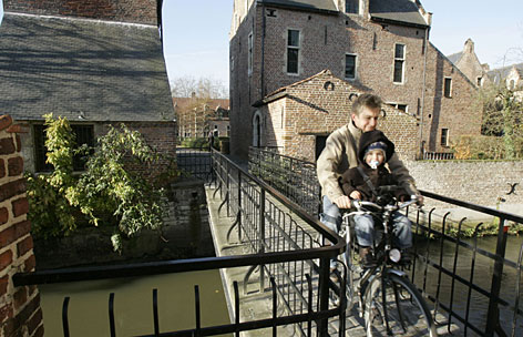 A father and his child cycle over a small canal at the beguinage in Leuven, Belgium. Once upon a time, the town was a sort of commune for unmarried, religiously-inclined women known as beguines (pronounced Bay-Gueens).