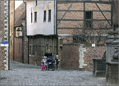 A mother with her children stroll through a street at the beguinage in Leuven, Belgium.