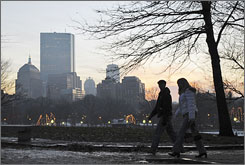 A couple walks through Boston Common past the Boston skyline at dusk on a December evening.