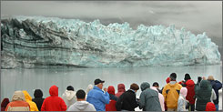Passengers aboard Holland America Line's Zaandam view the Margerie Glacier from the forward deck, while cruising in Glacier Bay National Park, Alaska.