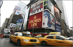 Taxi cabs make their way down Broadway under billboards advertising Broadway shows.