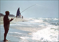 A man fishes off the beach at Gulf Shores, Ala. Tourism brochures call this stretch of glistening white sand on the Gulf of Mexico the Azalea Coast.
